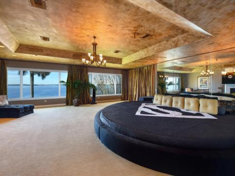 The master suite has a spacious walk-in closet, a mirrored wall, a gilded ceiling, and expansive views of the lake.