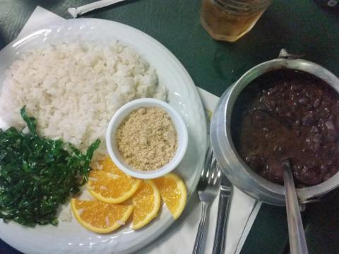It's sometimes served with farofa, — flour made from a root vegetable, cassava — shredded kale, rice, and oranges.