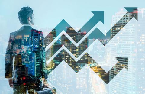Un joven líder empresarial, junto a unas gráficas sobre unos edificios