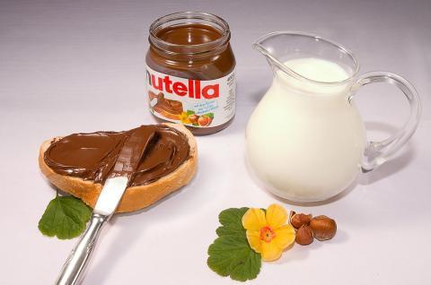 Un frasco de Nutella junto a una rebanada de pan y una jarra de leche