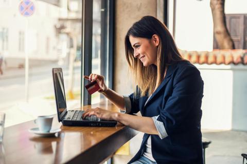 Una mujer paga en su ordenador con una tarjeta de crédito.