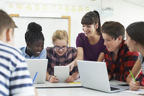 Una profesora enseña a alumnos con tablets y ordenadores