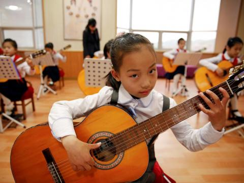 Schoolgirls learn to play guitar at the Mangyongdae Children's Palace in May 2016.
