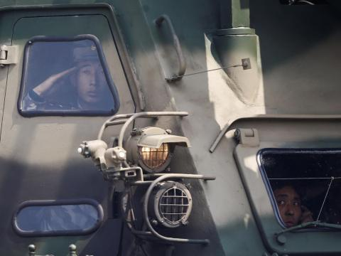 A soldier salutes from inside a vehicle carrying a missile as it drives past the stand with North Korean leader Kim Jong-un.
