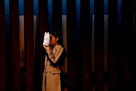 Una mujer sostiene una máscara tradicional de zorro para tomarse una foto en el santuario Meiji de Tokio, Japón, el 31 de diciembre de 2018.
