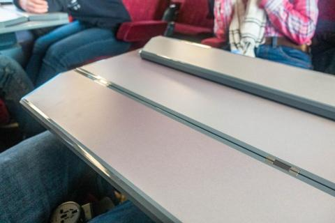 The tray table on the double rows folds out for each person. It's a much roomier table than you'd typically get from a seat-back on an airplane.