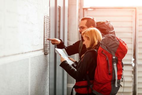 Turistas mochileros llegan a su piso de alquiler vacacional