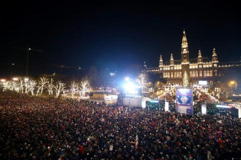 Los espectadores esperan a los fuegos artificiales en el ayuntamiento de Viena durante las celebraciones de Nochevieja en el 'Wiener Silvesterpfad' en Viena, Austria, el 31 de diciembre de 2018.