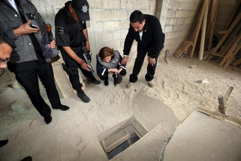 Mexican officials on July 12, 2015, look into the entrance of an escape tunnel used by Guzman.
