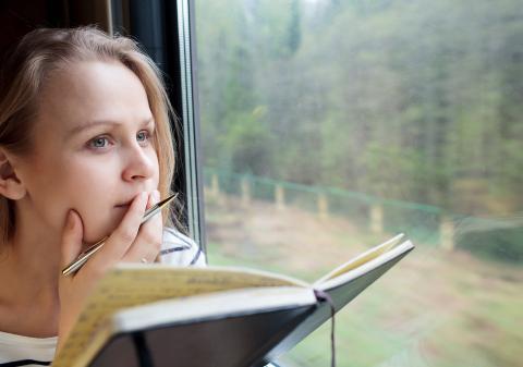 Chica viajando en un tren pensando con un cuaderno y bolígrafo en la mano