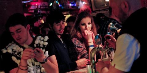 Personas pidiendo bebidas en la barra de un ba