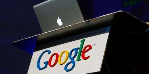 Un Macbook en una mesa colocado encima de un logo de Google