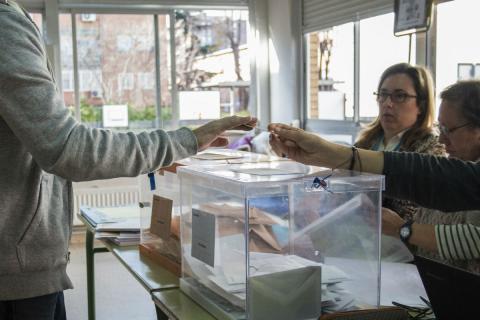 Un hombre enseña su DNI para votar en Madrid en 2015