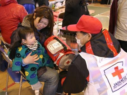 Un miembro de la cruz roja ayuda a un niño