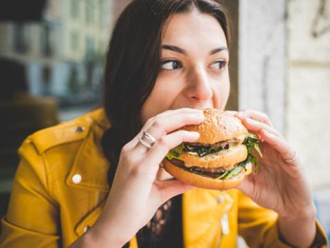 Una mujer se come una hamburguesa