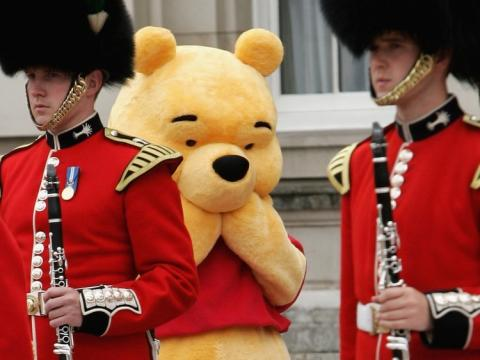 Una persona disfrazada de Winnie the Pooh se esconde tras dos soldados británicos
