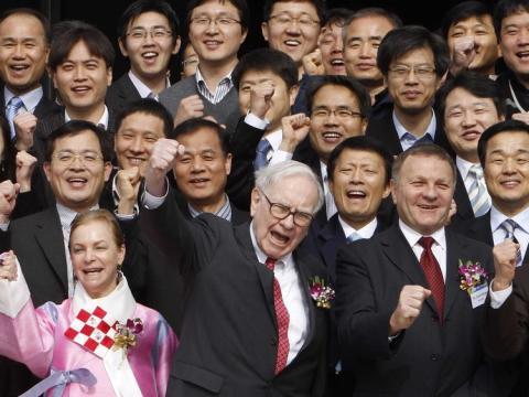 Warren Buffet celebrando algo junto a un gran grupo de personas