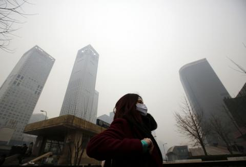 A woman makes her way through a heavy haze in Beijing.
