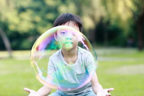 Un niño chino juega con una burbuja a punto de explotar.
