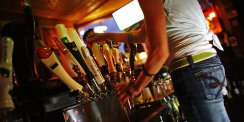 camarero sirviendo cerveza detrás de la barra del bar