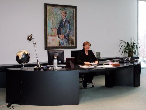 La canciller alemana, Angela Merkel, se sienta en su escritorio en su despacho de la cancillería de Berlín en 2006, frente a una pintura del primer canciller alemán, Konrad Adenauer.