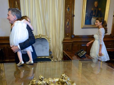 El presidente de Argentina, Mauricio Macri, lleva a su hija Antonia en brazos, seguido por su esposa Awada en el palacio presidencial de la Casa Rosada en Buenos Aires.