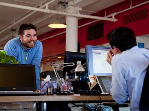 dos trabajadores hablan en la oficina