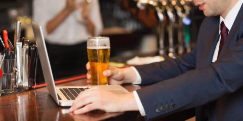 hombre bebiendo una cerveza y trabajando con su portátil en la barra de un bar