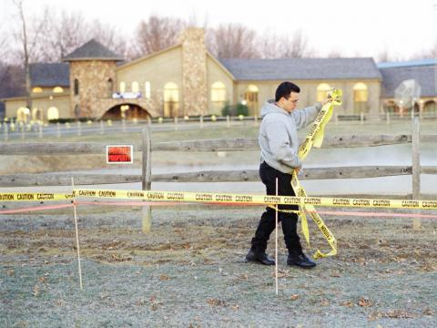 An unidentified man strings caution tape in front of the home of Mike Tyson near Southington, Ohio,