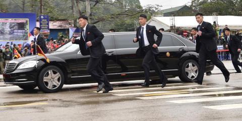 Guardaespaldas norcoreanos corren al lado de una limusina en la que viaja Kim a su llegada en la ciudad fronteriza de Dong Dang.