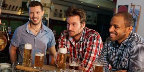 tres hombres bebiendo cerveza en un bar