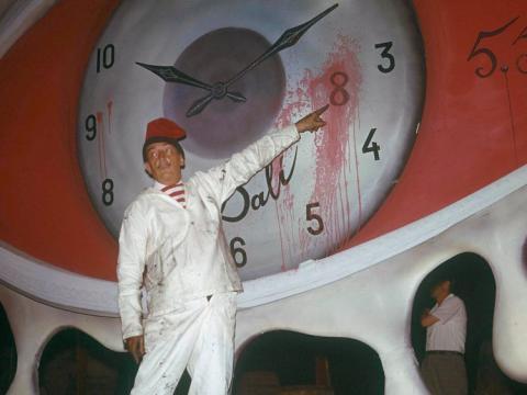 un hombre señala una pintura del reloj de Dali