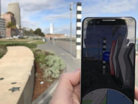 This is where the AR magic happens. When you hold your phone up to eye level, the standard map shrinks into a small circle at the bottom of the screen. The majority of your screen shows you the real world that's directly in front