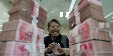 A woman sits between stacks of 100 yuan ($14.8) notes. A main argument for the social credit system is that many people still have no formal access to traditional banks and therefore need an alternative system to assess their trustworthiness.