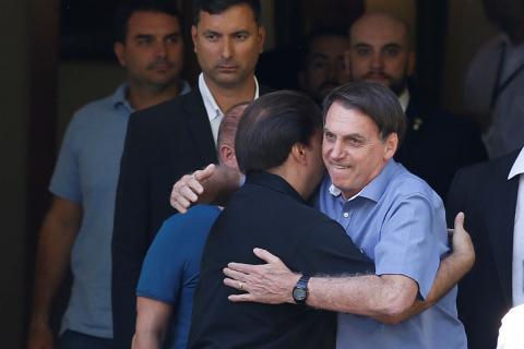 Jair Bolsonaro abraza a otro político tras una comida oficial.