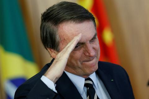 Jair Bolsonaro hace un saludo militar durante un evento.