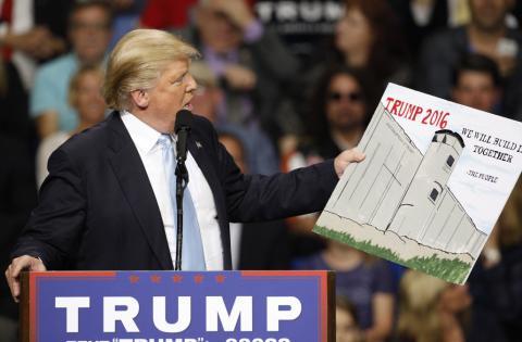 Trump muestra un cartel con el muro con México en la campaña de 2016.