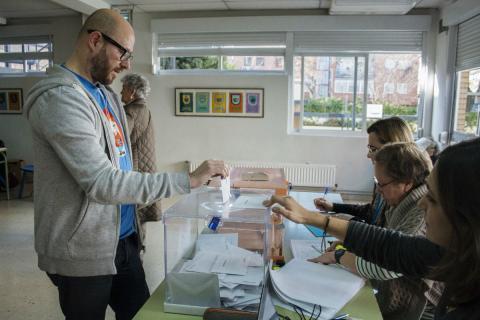 Un hombre deposita su voto en una urna en las elecciones generales de 2015