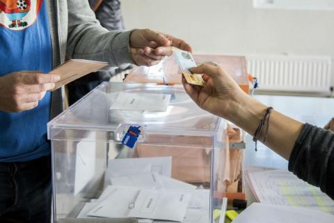 Un votante entrega su DNI en una mesa electoral