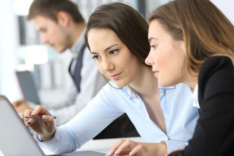 Una mujer enseña algo a su compañera en el trabajo.