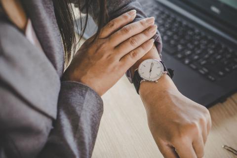 Una mujer mira su reloj en la oficina