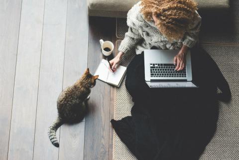 Una mujer trabaja junto a su gato.
