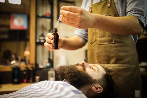 Un barbero aplica una loción a la barba de un hipster