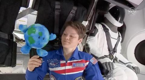 Astronaut Anne McClain plays with a plush Earth toy inside SpaceX's Crew Dragon capsule. The vehicle docked to the International Space Station on March 3, 2019, marking the first arrival of a human-rated commercial spaceship at