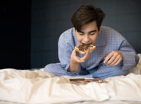 Chico comiendo sentado en la cama de su habitación