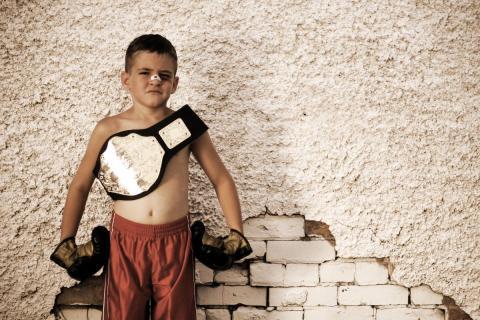 Un boxeador de categoría infantil con su cinturón de campeón