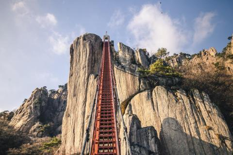 The Cloud Bridge at Daedunsan Mountain in South Korea slopes above a narrow canyon.