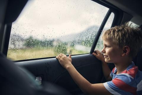 Un niño mirando por la ventana de un coche.