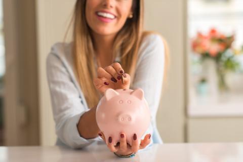 Mujer con una hucha ahorrando dinero.