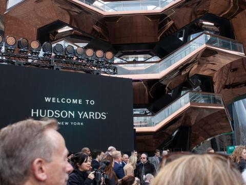 People gathered in Hudson Yards' central plaza for the morning's opening event. Chairs and a stage were set up for the planned performances and speeches from notable New Yorkers.